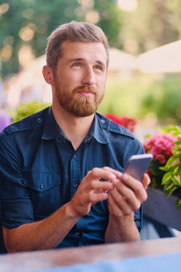 Varón barbudo del pelirrojo positivo usando un smartphone fotos de archivo libres de regalías