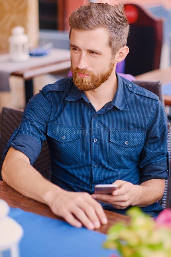 Varón barbudo del pelirrojo positivo usando un smartphone fotografía de archivo libre de regalías