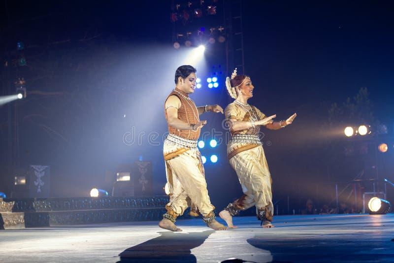 Varón clásico de dos bailarines de Odissi y danza de ejecución femenina de Odissi en etapa en el templo de Konark, Odisha, la Ind imagenes de archivo