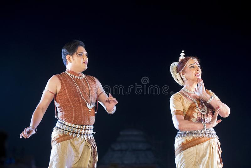 Varón clásico de dos bailarines de Odissi y danza de ejecución femenina de Odissi en etapa en el templo de Konark, Odisha, la Ind imagen de archivo libre de regalías