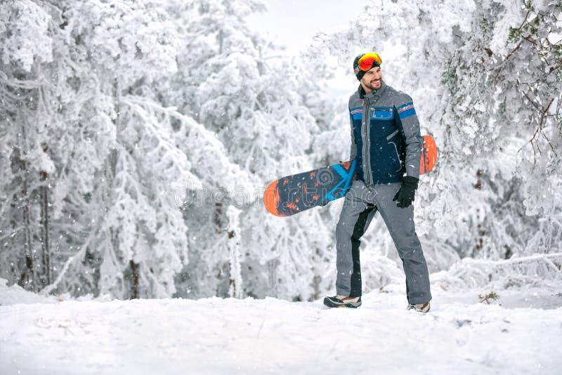 Varón con la snowboard en montaña imagenes de archivo