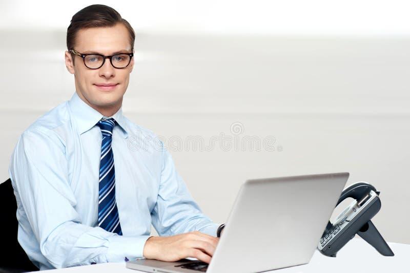 Varón corporativo hermoso que ata en la computadora portátil imagenes de archivo