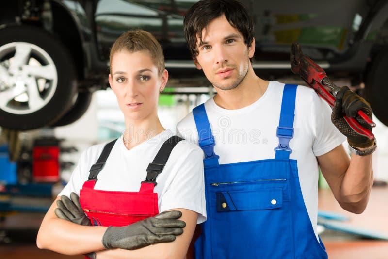 Varón de los mecánicos de coche y hembra delante del auto fotos de archivo libres de regalías