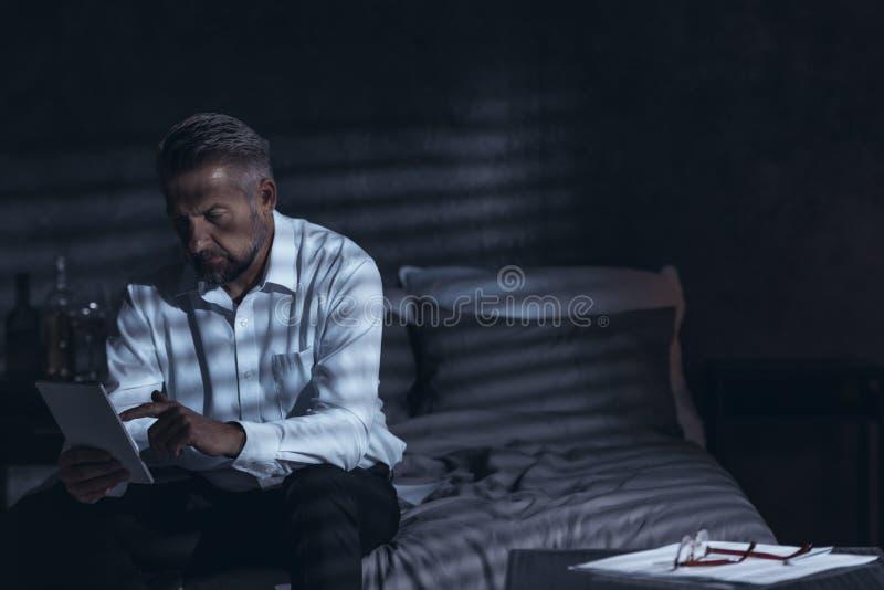 Varón de mediana edad agotado que se sienta en una cama en una habitación en n foto de archivo