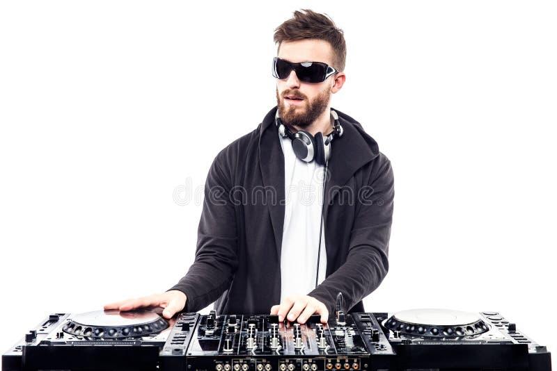 Varón de moda DJ que presenta contra la consola de mezcla imagen de archivo