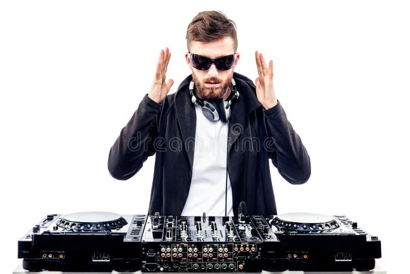 Varón de moda DJ que presenta contra la consola de mezcla imágenes de archivo libres de regalías