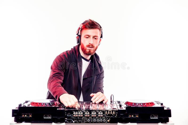 Varón de moda DJ que presenta contra la consola de mezcla foto de archivo libre de regalías