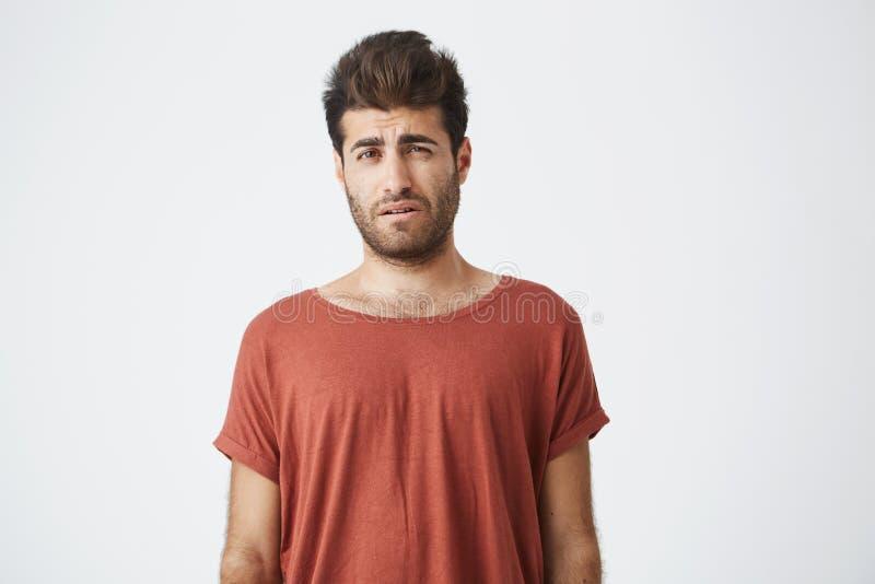 Varón elegante barbudo que descontenta la mirada que se opone en paño casual al fondo blanco Hombre joven que tiene alguno imagenes de archivo