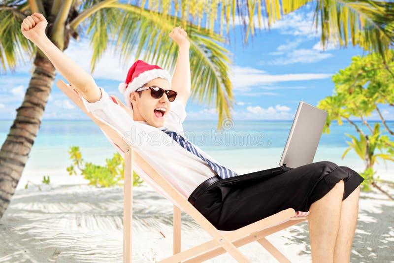 Varón emocionado con el sombrero de santa que se sienta en una silla y que trabaja en a foto de archivo