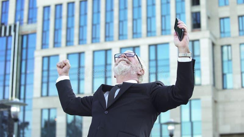 Varón emocionado del negocio en el traje que muestra el móvil de la tenencia de la muestra del éxito, logro foto de archivo