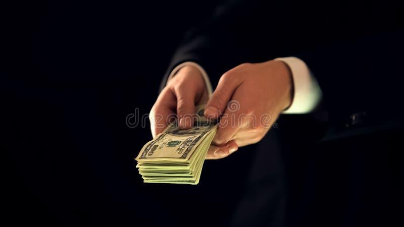 Varón en el manojo de billetes de banco del dólar, competencia desleal, corrupción de la tenencia del traje imágenes de archivo libres de regalías