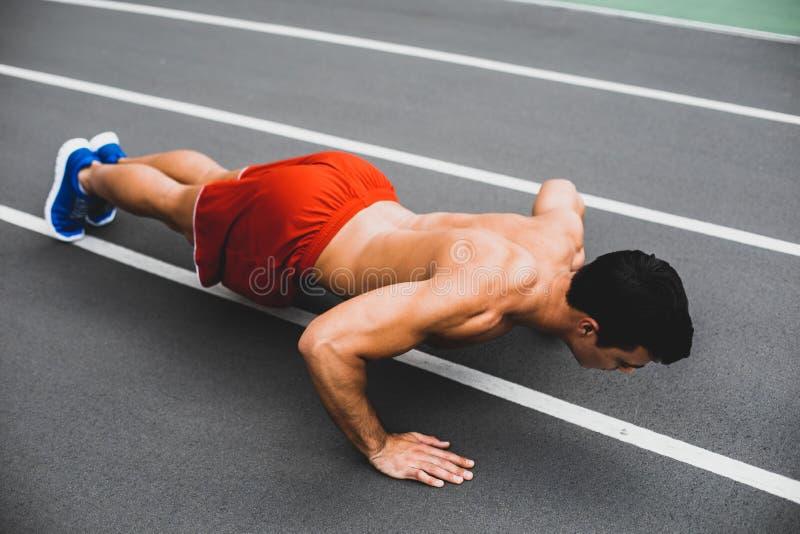 Varón enfocado con el cuerpo atractivo que hace ejercicios imagen de archivo
