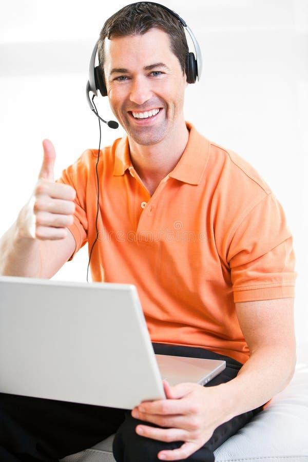 Varón feliz del negocio en el ordenador portátil con las auriculares en la sonrisa foto de archivo