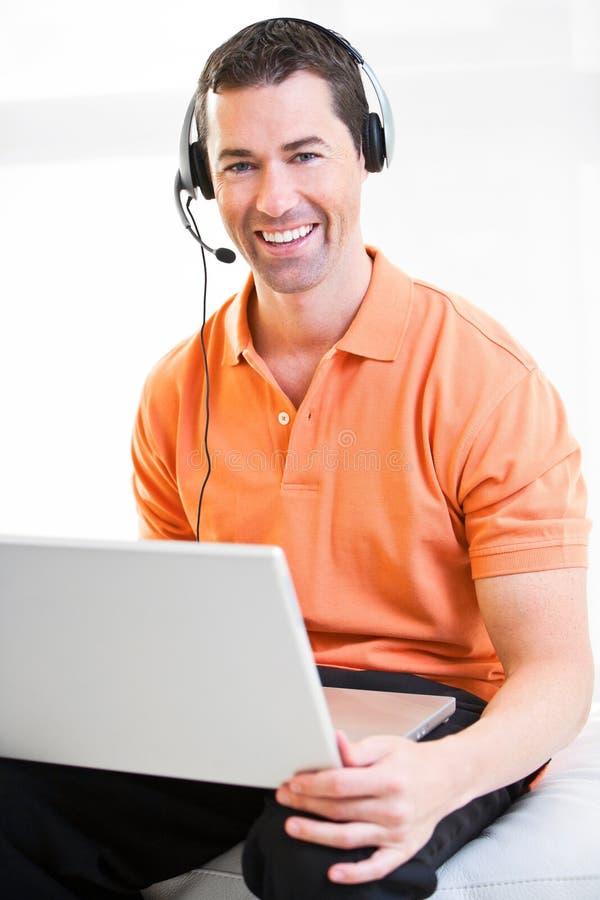 Varón feliz del negocio en el ordenador portátil con las auriculares en la sonrisa imagenes de archivo