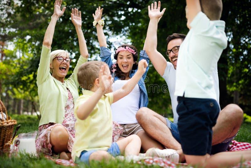Varón feliz y comida campestre que juega y de goce femenina con los niños afuera fotografía de archivo