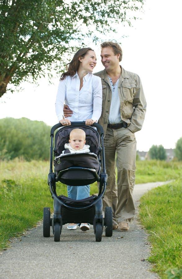 Varón feliz y padres femeninos que caminan con su niño en carro de bebé fotos de archivo libres de regalías