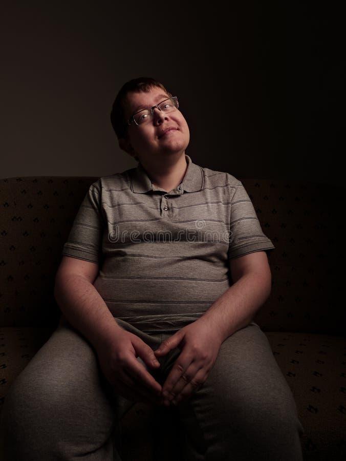 Varón gordo perezoso que se sienta en el sofá y que mira algo imágenes de archivo libres de regalías