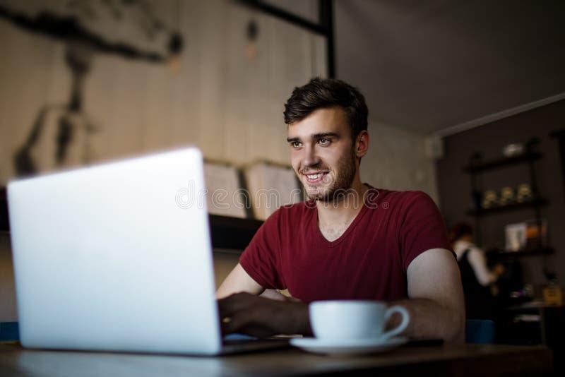 Varón hermoso alegre que tiene llamada en línea vía netbook durante tiempo de la reconstrucción en restaurante fotos de archivo