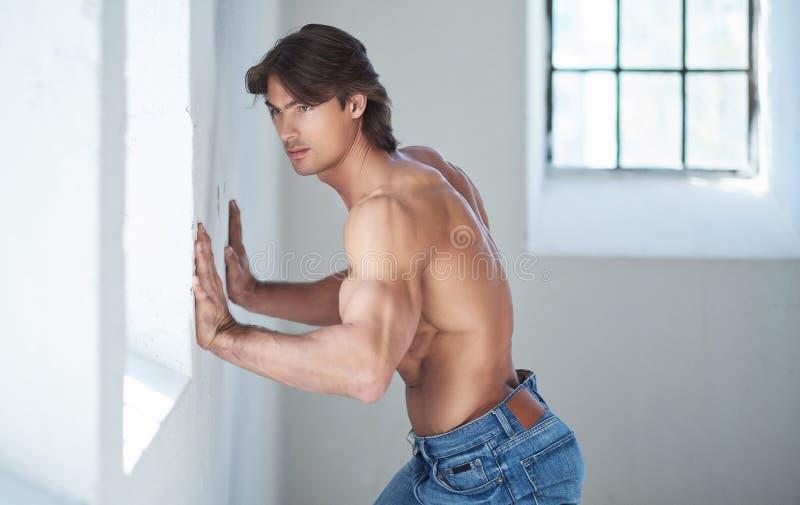Varón hermoso descamisado con un cuerpo muscular perfecto que se inclina en una pared en el estudio, mirando una ventana fotos de archivo libres de regalías