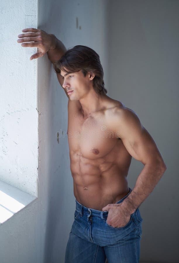 Varón hermoso descamisado con un cuerpo muscular perfecto que se inclina en una pared en el estudio, mirando una ventana imagen de archivo libre de regalías
