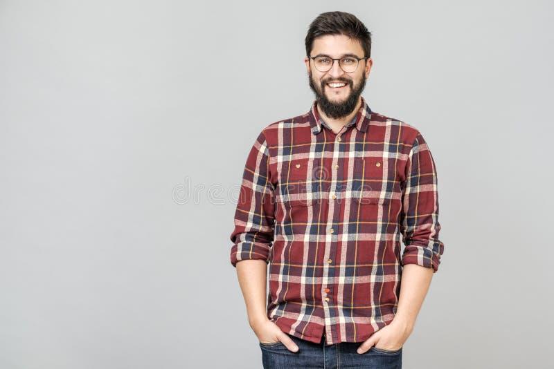 Varón hermoso joven con la barba contra fondo gris imagenes de archivo