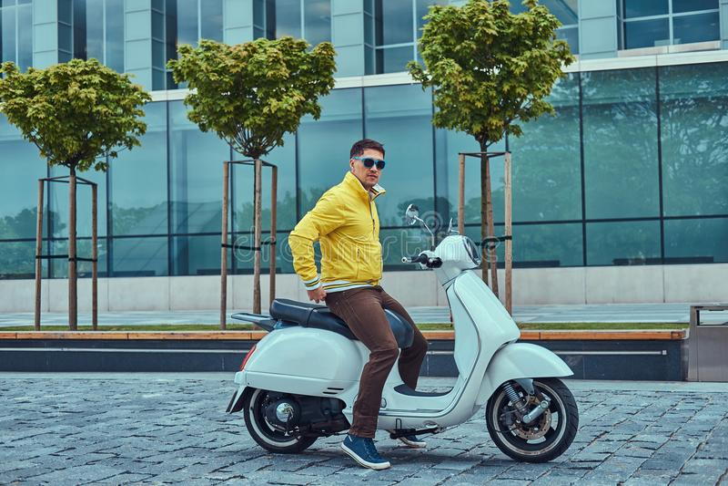 Varón hermoso que lleva los pantalones marrones chaqueta amarilla y gafas de sol, sentándose en una vespa italiana clásica blanca imágenes de archivo libres de regalías