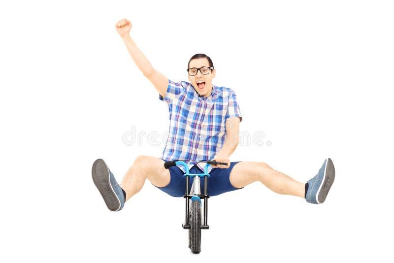 Varón joven emocionado que monta una pequeña bicicleta y que gesticula happines fotografía de archivo libre de regalías