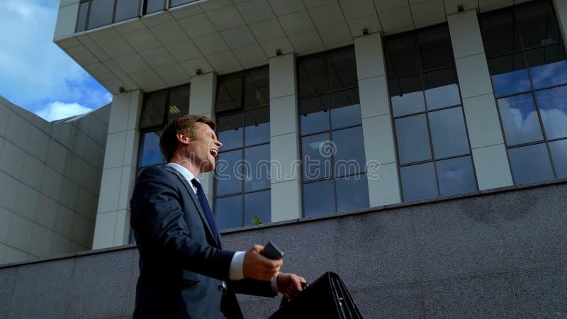 Varón joven en el traje de negocios feliz con éxito de las noticias en la operación financiera foto de archivo