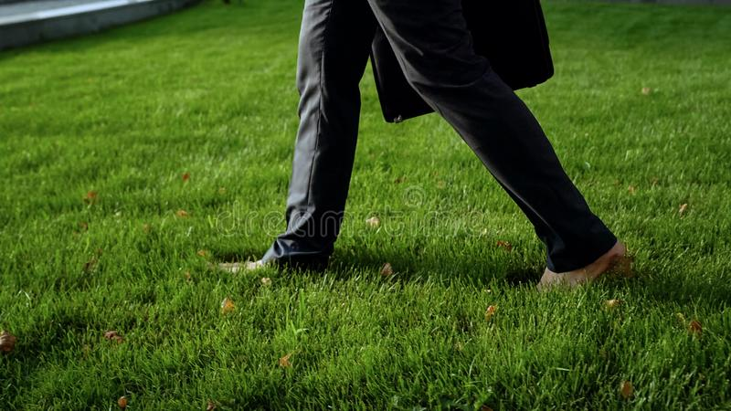 Varón joven en traje formal que camina descalzo en la hierba verde, relajándose después de la tensión imágenes de archivo libres de regalías