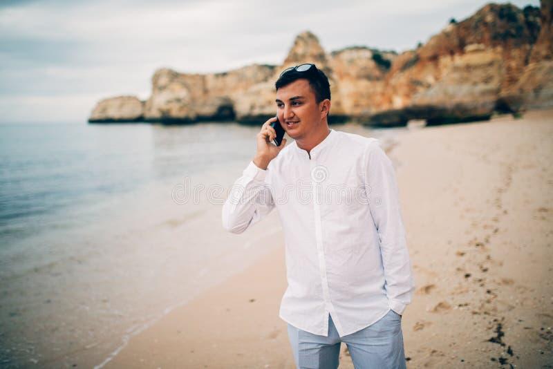 Varón joven hermoso que camina en la playa y que habla en el teléfono móvil Concepto de la comunicación fotos de archivo