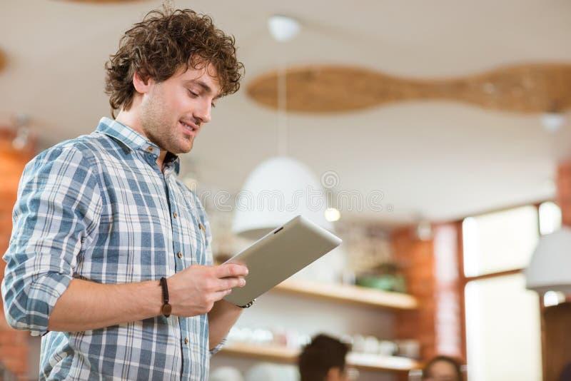 Varón joven rizado sonriente pensativo atractivo usando la tableta en casa imagenes de archivo
