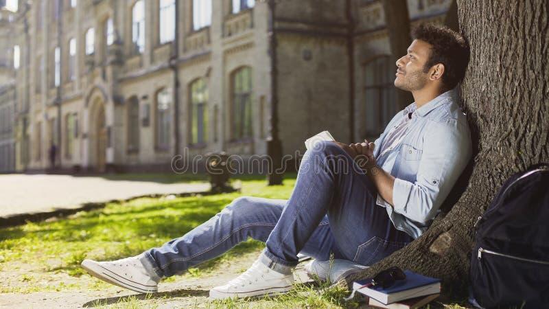 Varón joven soñador que se sienta con el cuaderno debajo del árbol, pensando qué escribir, idea fotografía de archivo