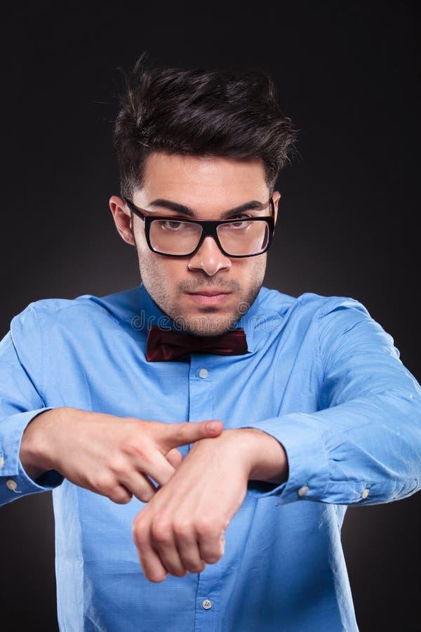 Varón joven trastornado que señala en el reloj imaginario y que mira fijamente adelante imagen de archivo