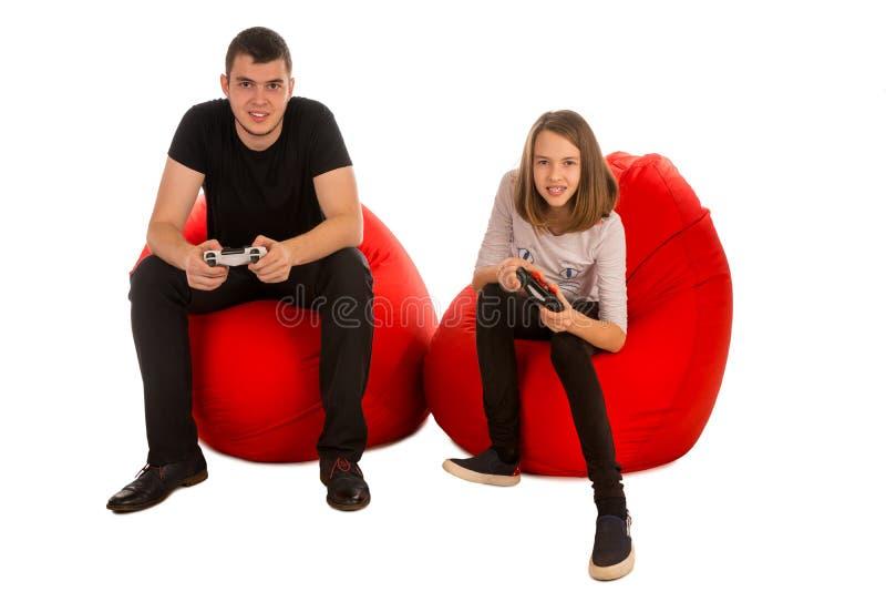 Varón joven y muchacha divertida que juegan a los videojuegos mientras que se sienta en r imagen de archivo