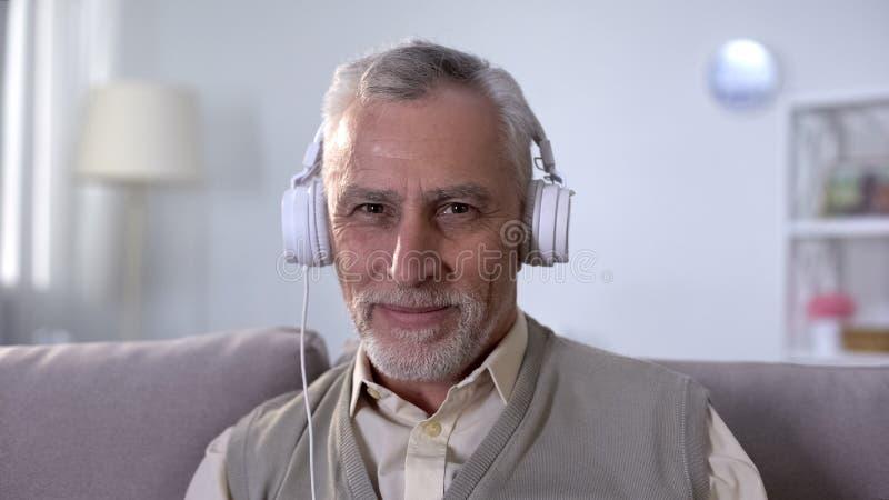 Varón mayor alegre en auriculares que escucha la música, disfrutando de melodía preferida foto de archivo