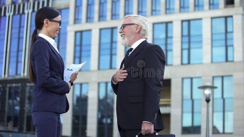 Varón mayor en socio femenino joven de la reunión del traje de negocios cerca del centro de la oficina fotos de archivo libres de regalías
