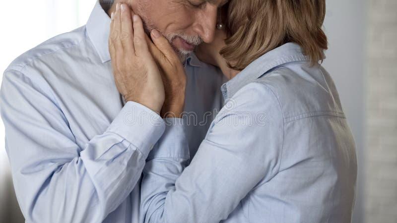 Varón mayor y abrazo femenino, mejilla masculina de ahuecamiento de la señora, matrimonio largo feliz foto de archivo