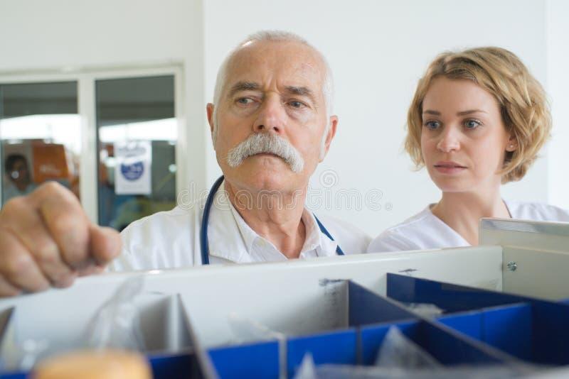 Varón mayor y compañeros jovenes de los doctores de la hembra imagen de archivo libre de regalías