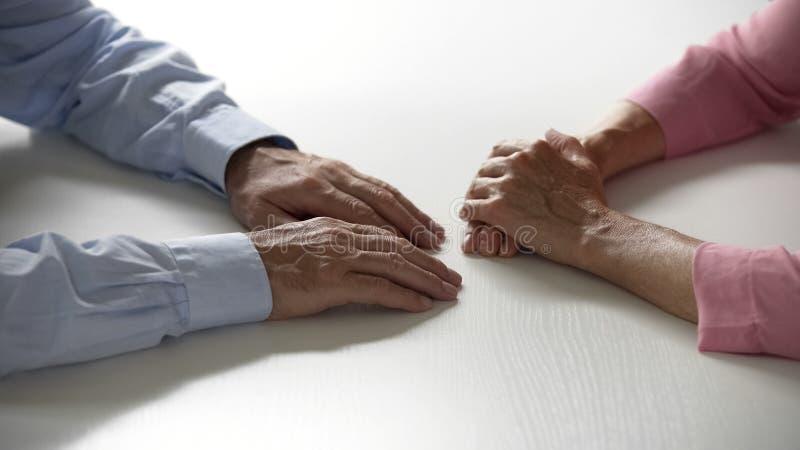 Varón mayor y manos femeninas que mienten en relaciones del amor y del cuidado de la tabla en matrimonio fotos de archivo