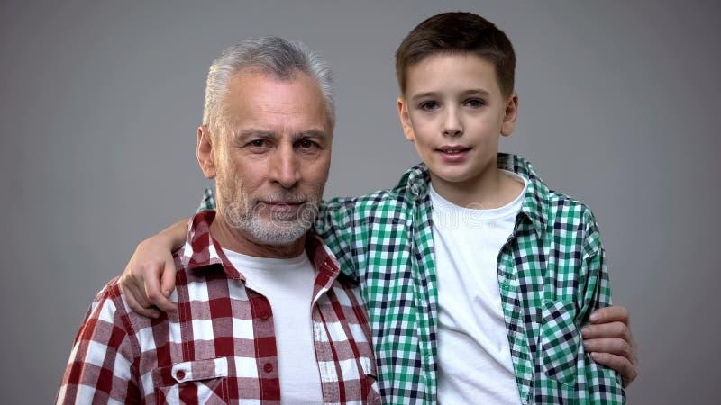 Varón mayor y niño pequeño que abrazan y que miran a la cámara, relaciones amistosas imagen de archivo libre de regalías