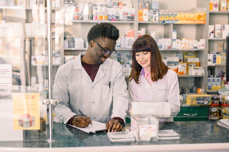 Varón multiethnical confiado y farmacéuticos de sexo femenino en farmacia Farmacéutico afroamericano del hombre que hace notas en foto de archivo