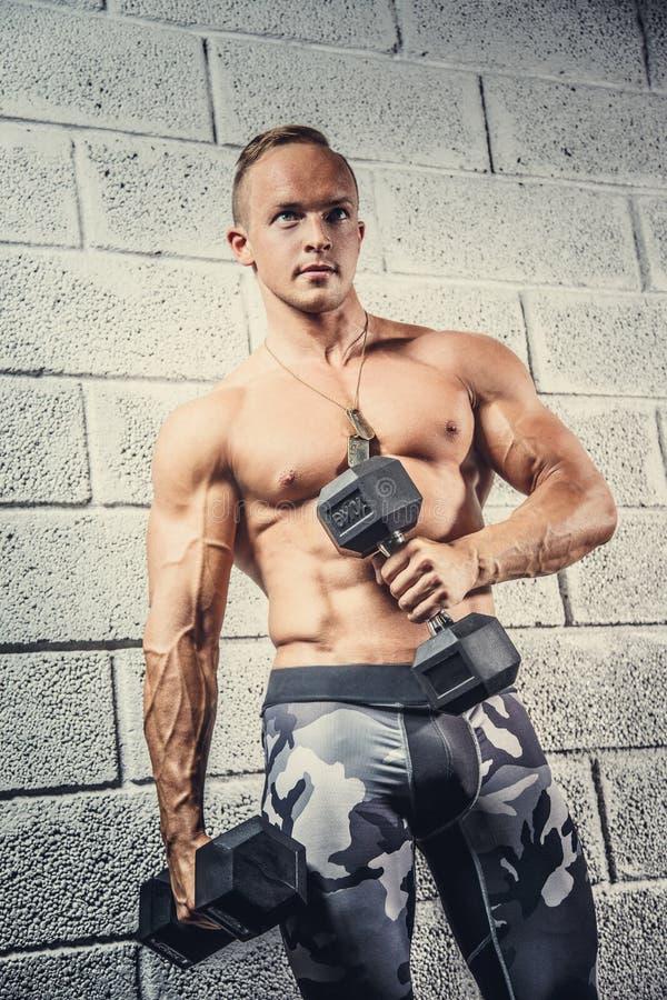 Varón muscular impresionante en pantalones miliraty foto de archivo libre de regalías