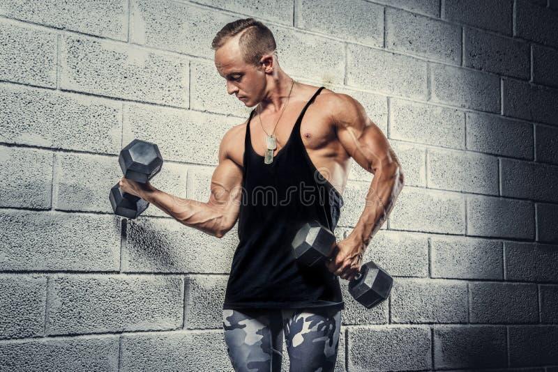 Varón muscular impresionante en pantalones miliraty imagenes de archivo