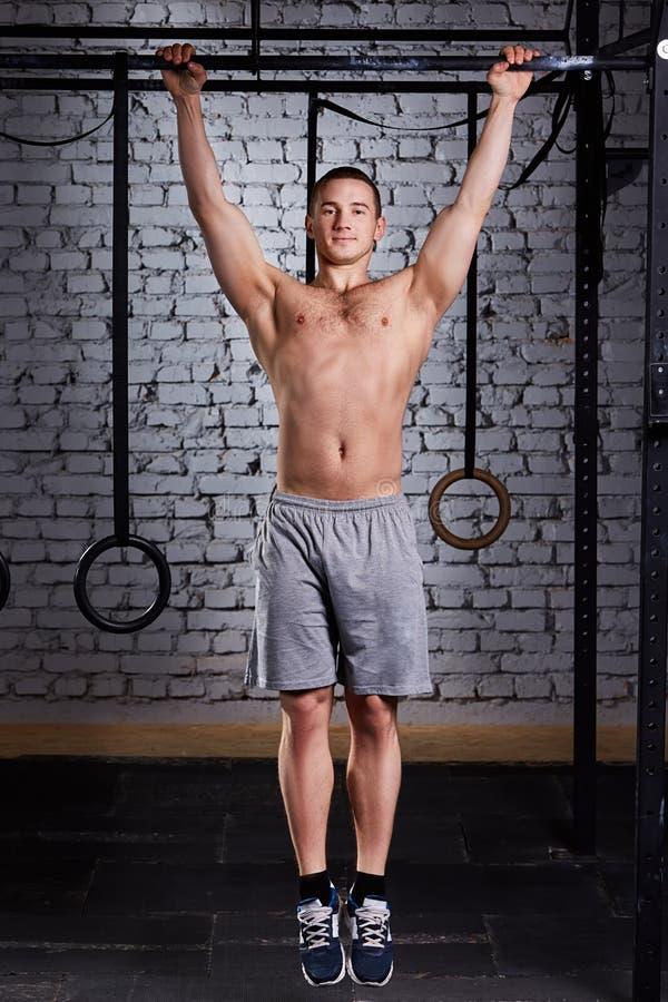 Varón muscular joven que hace ejercicios en barra horizontal en un club del gimnasio contra la pared de ladrillo fotografía de archivo libre de regalías