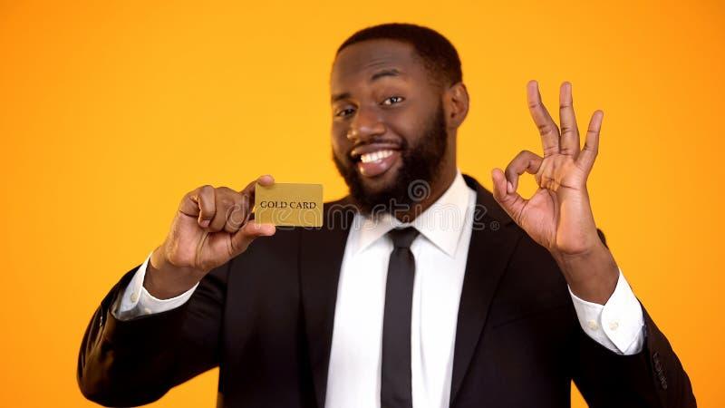 Varón negro hermoso alegre en el traje que muestra la tarjeta y el gesto de la autorización, éxito del oro imagen de archivo libre de regalías