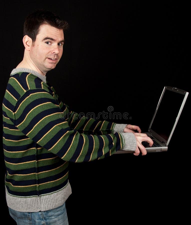 Varón ocasional en la computadora portátil con gota negra de la pantalla imagen de archivo