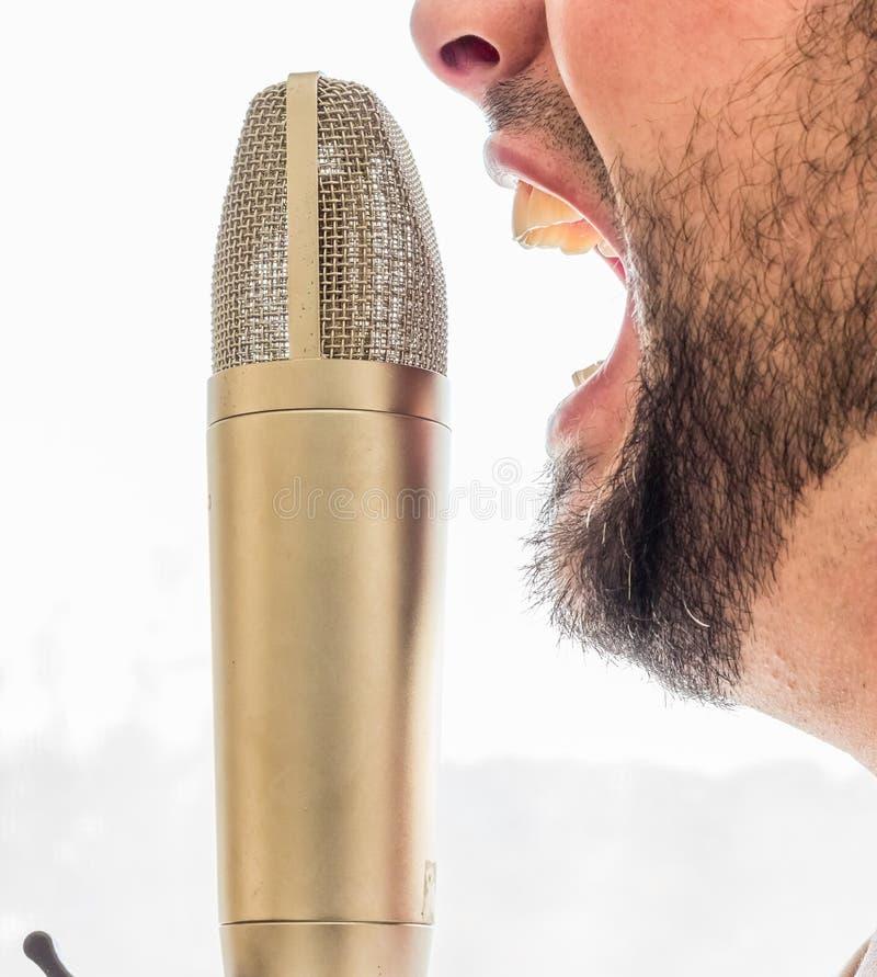 Varón que grita en un micrófono foto de archivo