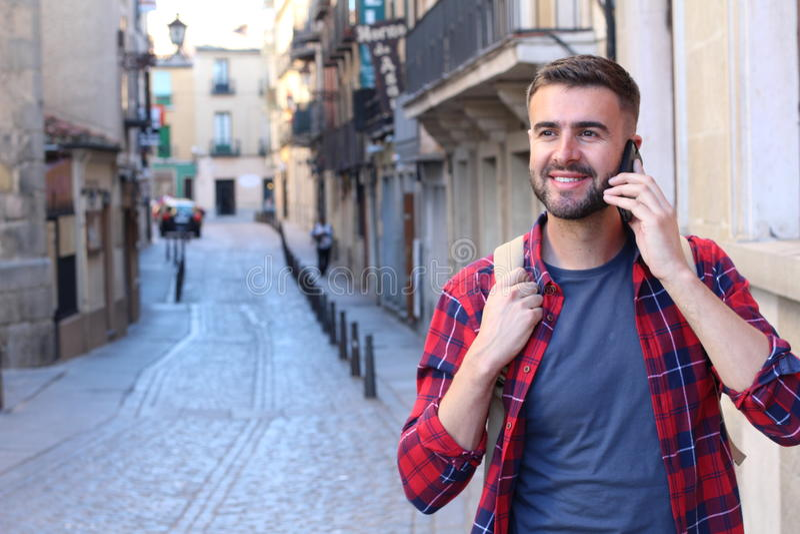 Varón que hace una llamada mientras que da un paseo alrededor de ciudad foto de archivo