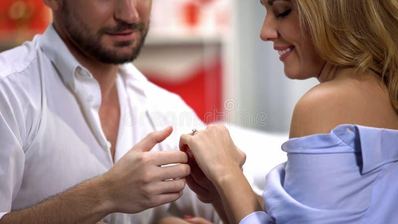 Varón que lleva a cabo blando la mano de la mujer con el anillo de compromiso, matrimonio de la oferta, amor foto de archivo