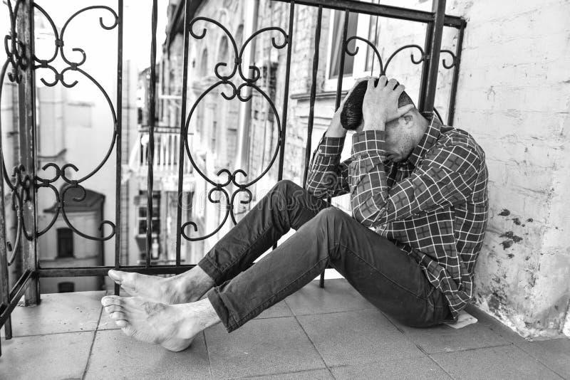 Varón que se sienta en el balcón La persona siente dolor emocional y desamparo terribles El malo del adicto imagen de archivo